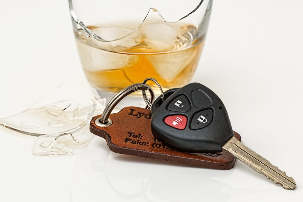 How long will a DUI stay on your record? Stock image of a broken glass with ice and amber liquid inside it and a set of car keys by Steve Buissinne from Pixabay